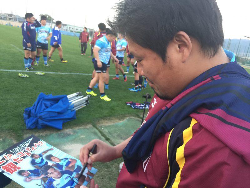 摂南大学特製クリアファイルにサインをする近鉄・樫本敦選手。